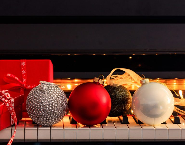 Chritmas balls and gift boxes on piano keyboard, front view. Xmas music, songs, greeting card template, copy space